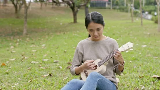 Thumbnail for Asian Woman enjoy play ukulele and song in the park
