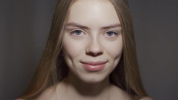 Mädchen posiert auf einem grauen Hintergrund. Nahaufnahme. Konzept - Kosmetik, Kosmetik, Saubere Haut