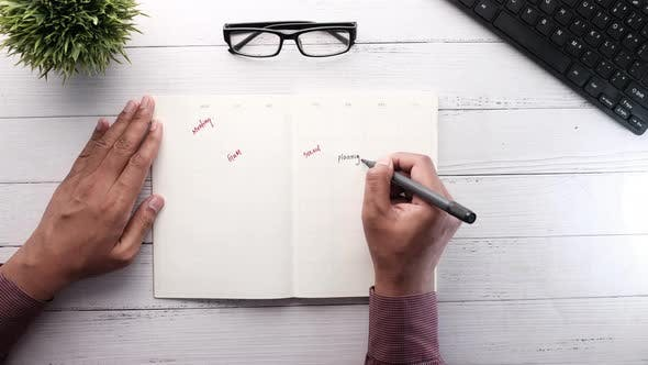 Person Hand Writing Plans on Notepad on Desk.