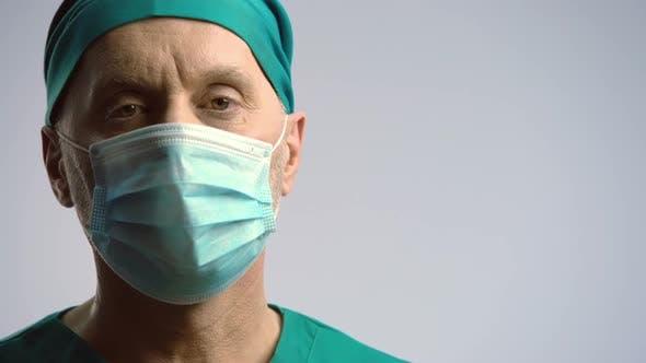 Thumbnail for Ernstes Gesicht des Chirurgen in der medizinischen Gesichtsmaske Blick auf die Kamera, Krankenversicherung
