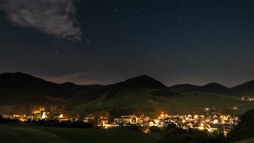 Starry Night Sky with Stars over Rural Village with Traffic and Street Lighting
