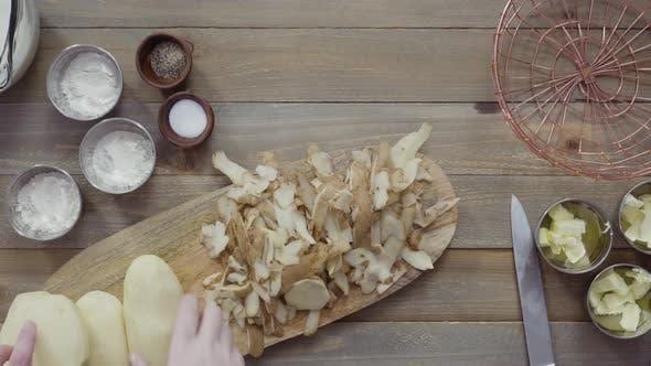 Flat lay. Peeling organic yellow potatoes with potato peeler