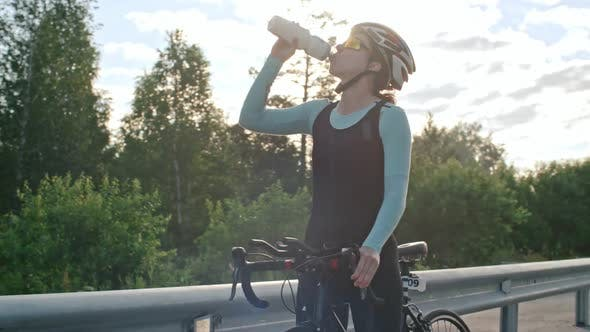Thumbnail for Cheerful Cyclist Drinking Water