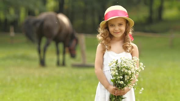 Thumbnail for Little Girl Is Standing in a Park with a Bouquet of Wildflowers. Slow Motion