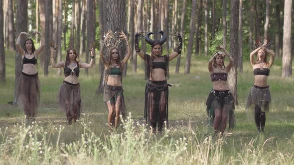 Thumbnail for Young Women in Theatrical Costumes of Forest Dwellers or Devils Dancing Arabic Dance in Forest