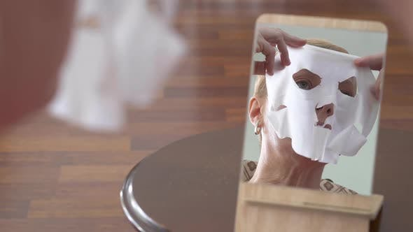 Beautiful Elderly Woman Looking at the Mirror and Applying Sheet Mask for Face at Home
