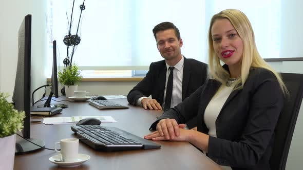 Thumbnail for Two office workers, man and woman, sit at desks with computers and talk to the camera, smiling
