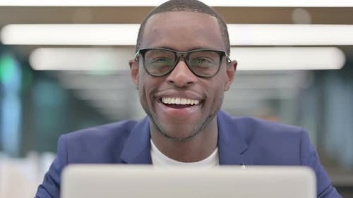 African Businessman with Laptop Smiling at Camera