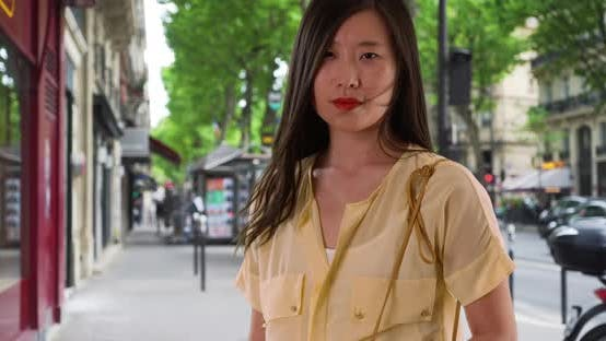 Portrait of Chinese woman standing on windy Paris street looking at camera