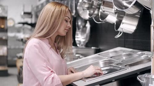 The Beautiful Woman Is Checking the Stainless Steel Tableware