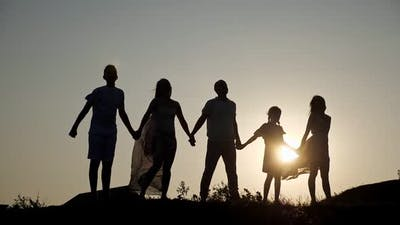 Silhouettes of Family Raising Hands on Hill Under Clear Sky