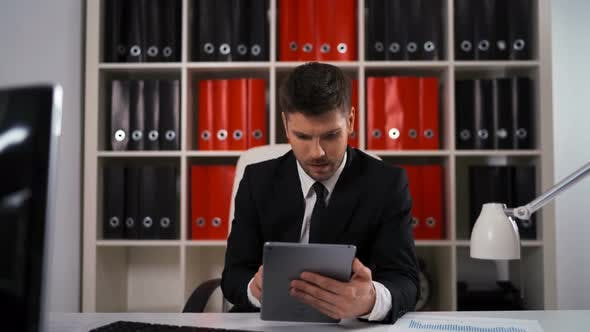 Thumbnail for Businessman Writing Notes From Ipad in Business Office