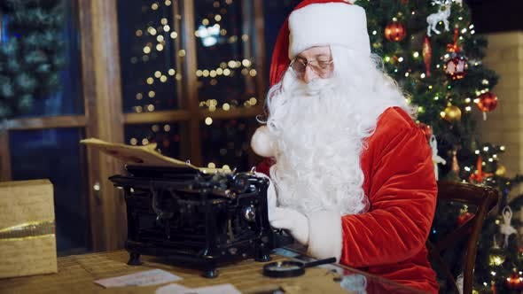 Thumbnail for Santa Claus in a Traditional Red Costume is Writing a Letter on the Typewriter