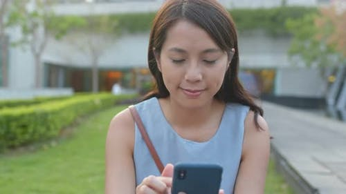 Woman look at the mobile phone in park
