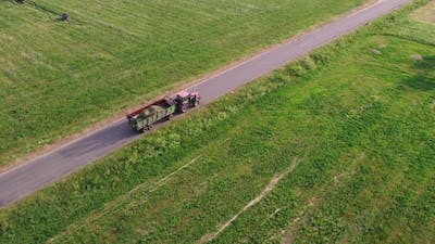 Tractor Carries a Trailer with Hay Through the Countryside