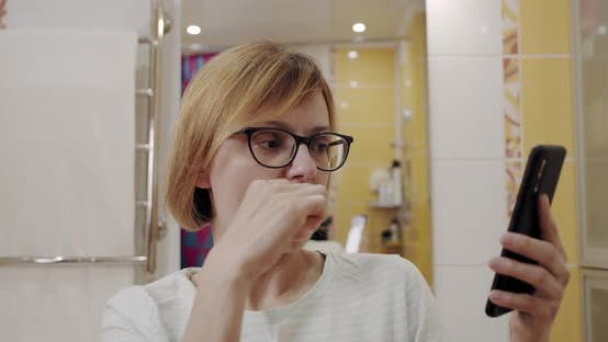 Thumbnail for Beautiful Carefree Woman Cleaning Her Teeth with Toothbrush and Browsing Apps on Her Smartphone