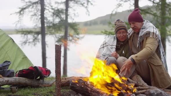 Thumbnail for Romantic Senior Couple Sitting Under Blanket by Campfire and Talking