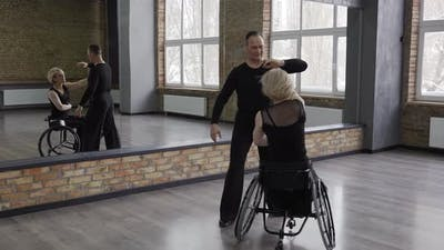 Positive Middle Aged Couple Dancing in Ballroom