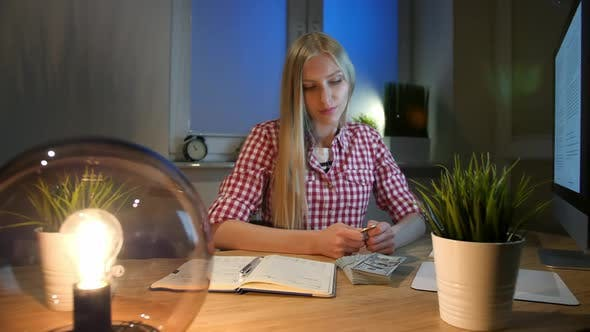 Blond Woman at Desk Looking at Bitcoin. Beautiful Young Blond Female Sitting at Workplace with