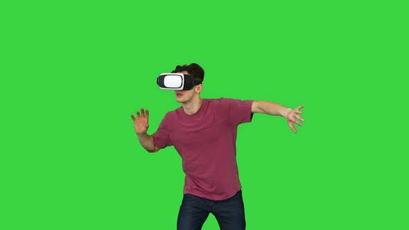 Amazed Man Using VR Headset Glasses Touching and Interacting with Virtual Reality World on a Green