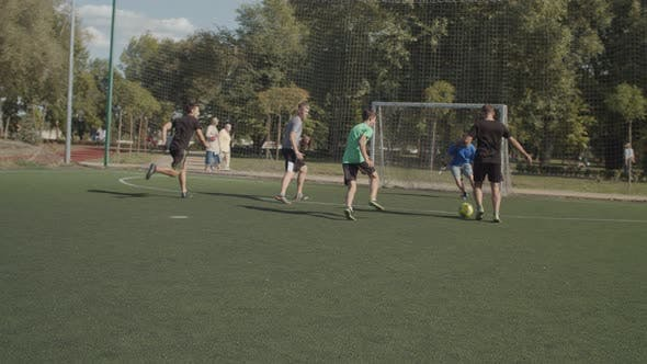 Cheerful Footballers Celebrating a Goal on Pitch