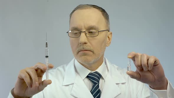 Thumbnail for Doctor Holding Syringe and Ampoule, Prescribing Effective Medication to Patient
