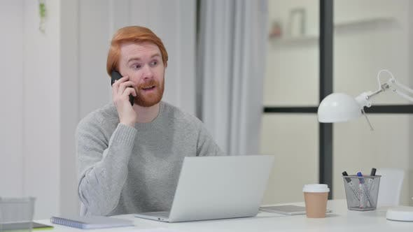 Thumbnail for Redhead Man with Laptop Talking on Smartphone
