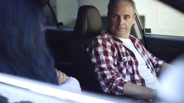 Portrait of Sad Serious Caucasian Man Sitting on Driver's Seat Arguing with Woman with Crossed Hands