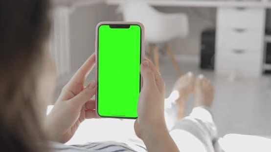 Thumbnail for Women sitting on Couch and watching a smartphone with a green screen. POV