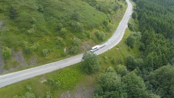 Thumbnail for White Transportation Van or Bus Driving Along Winding Mountain Road with Green Hills, Aerial View