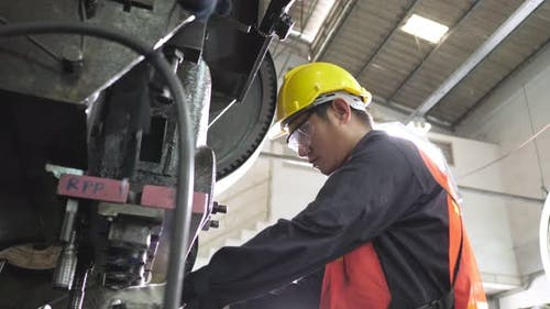 Asian worker operate stamping machine working wear safety uniform