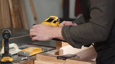 Carpenter Prepares the Drill Tool for Work