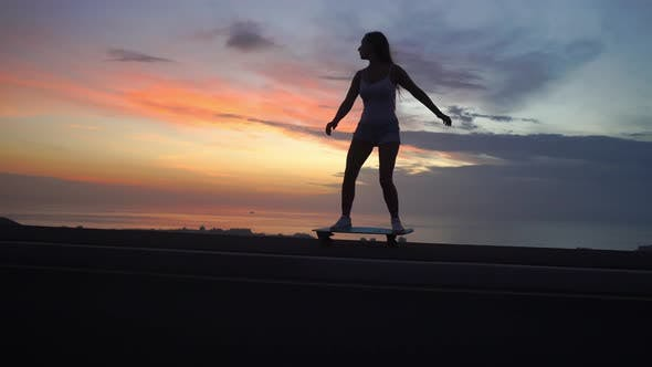 Thumbnail for Beautiful Girl Rides a Skateboard on the Road Against the Sunset Sky