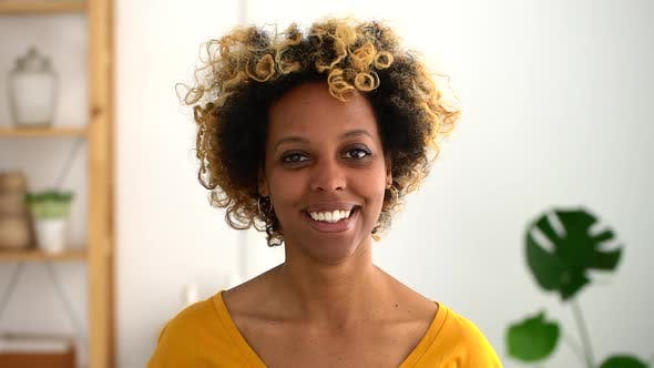 Thumbnail for Headshot of African Woman Smiling Indoors Spbd. Female with Bleached Curly Hair Look at Camera