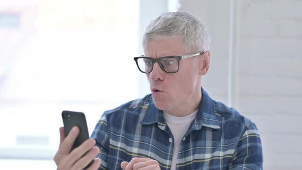 Thumbnail for Portrait of Casual Middle Aged Man Reacting To Failure on Smartphone