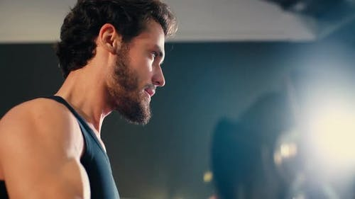 Close-up of Face of Young Man with Muscular Body Doing Exercise with Weights.