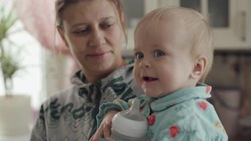 Femme Mère Avec Bébé Sur Ses Bras Cuisine À La Maison