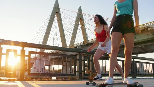 Thumbnail for Young Women Riding Skateboards on the Waterfront - Big Urban Bridge on Sunset