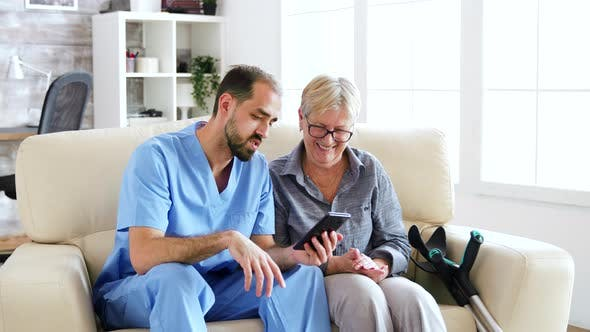 Cover Image for Male Doctor Teaching Senior Woman How To Use Her Phone