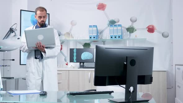 Thumbnail for Doctor in His Modern Office Standing and Typing at His Laptop