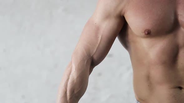 Muskulöser Sportler posiert im Fitnessstudio. Schöner Sport männlicher Körper