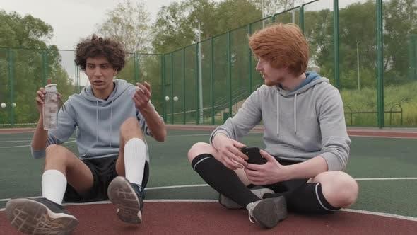 Amis reposant sur un terrain de basket-ball extérieur