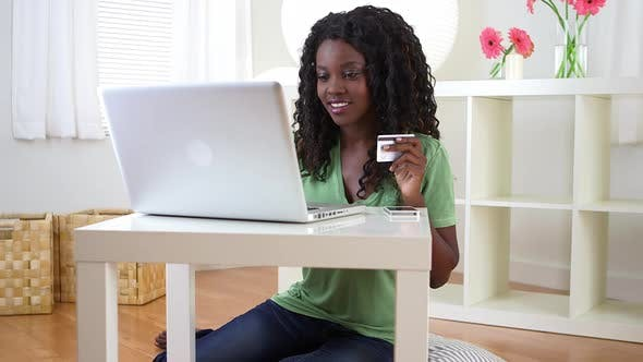 Thumbnail for Happy black teenager typing in card information