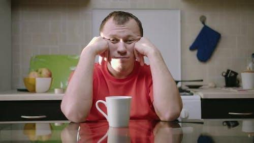 Müder Emotionsloser Mann mit einem leeren Blick Sieht direkt aus und unterstützt seinen Kopf mit seinen Händen
