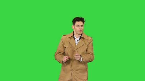 Young Man Wearing Trench Coat Dancing and Having Fun on a Green Screen, Chroma Key
