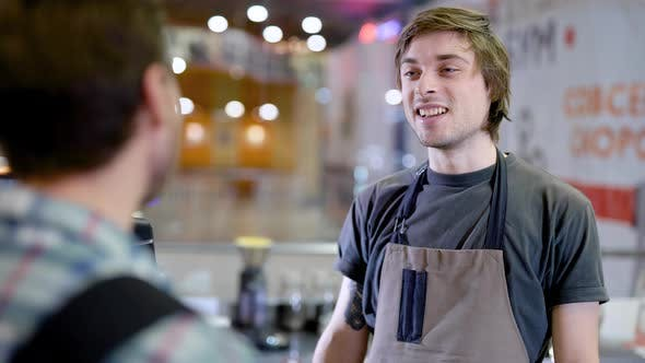Thumbnail for Young Male Barman Is Listening To an Order of Visitor Man in a Bar of Cozy Restaurant in Daytime