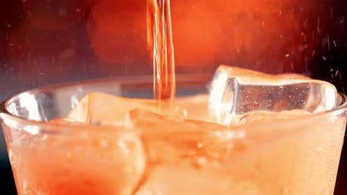 Glass of Soft Drink. Ice Soft Drink with Splashing Bubbles Slow Motion on a Blurry Light