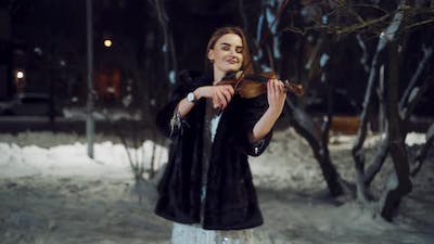 Playing Violin Instrument in the Winter Time