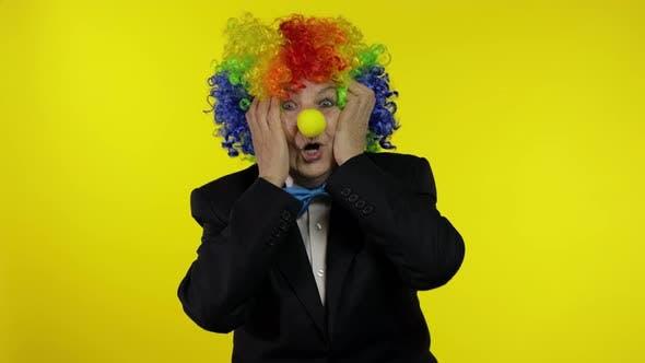 Thumbnail for Senior Old Woman Clown in bunten Perücke sieht überraschend schockiert aus. Erstaunen