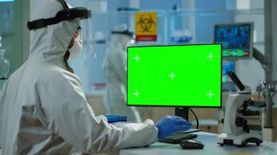 Man Researcher in Coverall Looking at Chroma Key Computer